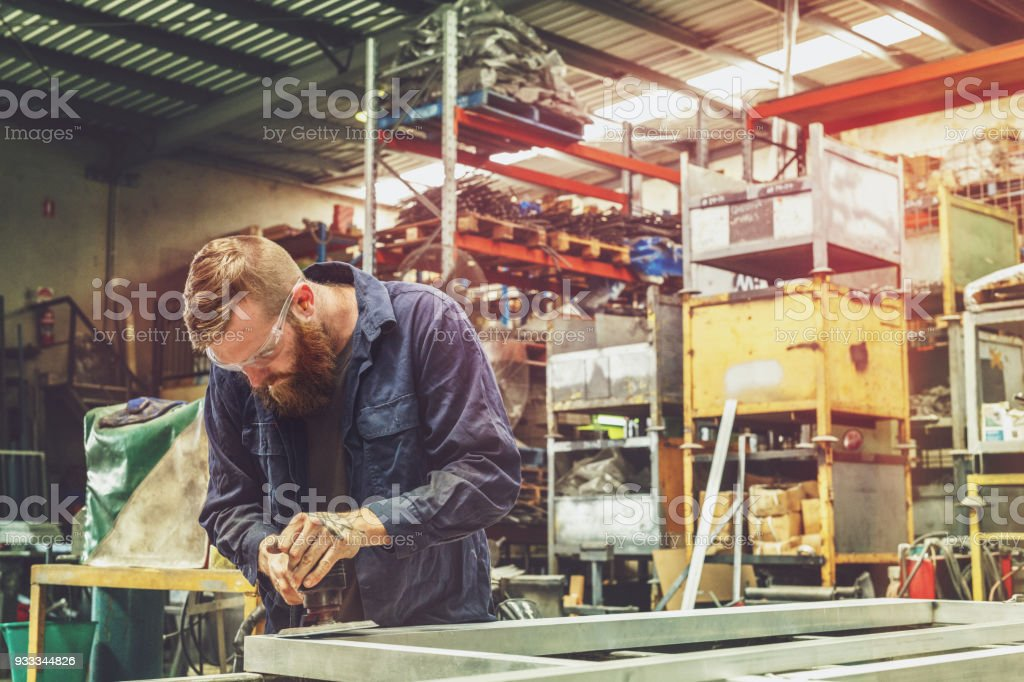 Young Metal Worker Using Power Tool In Factory With Protective Equipment stock photo