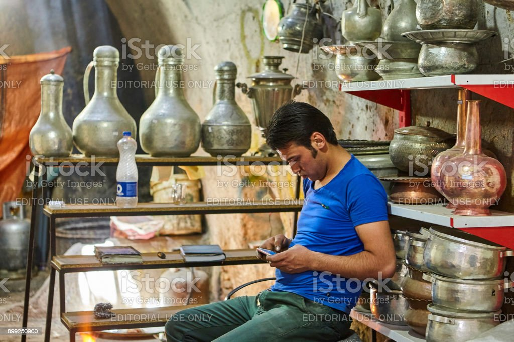 Young metalware seller plays games on smartphone, Yazd, Iran. stock photo