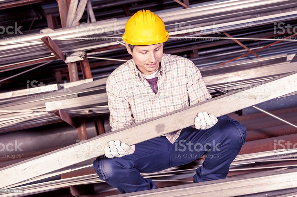 young metalworker controls some metal bars in steel mill stock photo