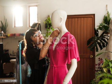 A young mexican dressmaker fixing a dress in a shop.