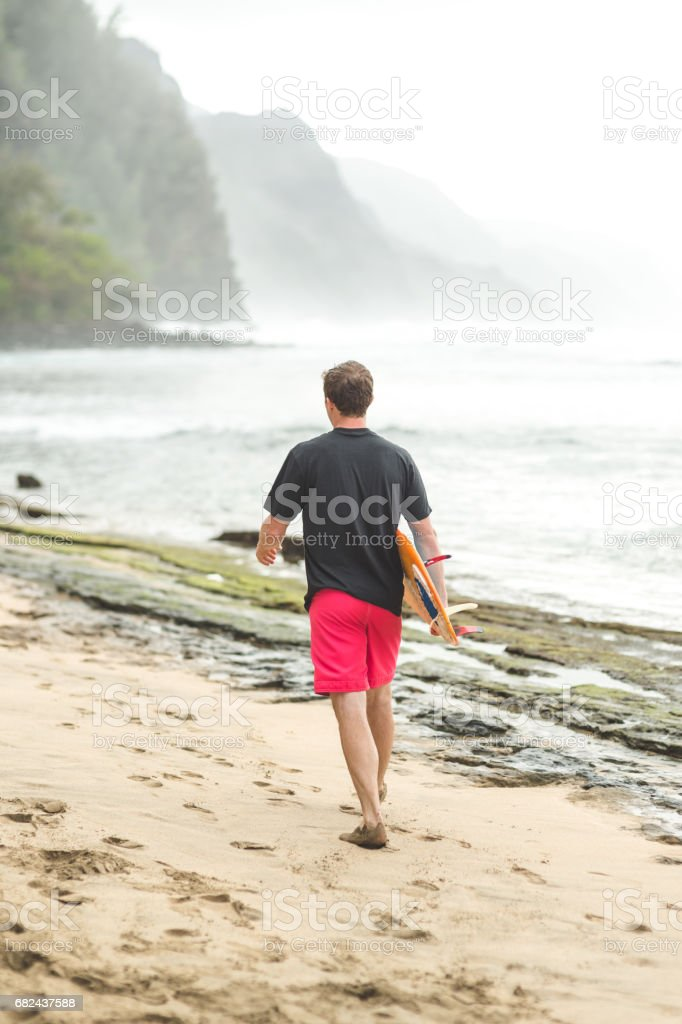 Young mid-20s man carrying surfboard on Hawaii beach royalty-free stock photo