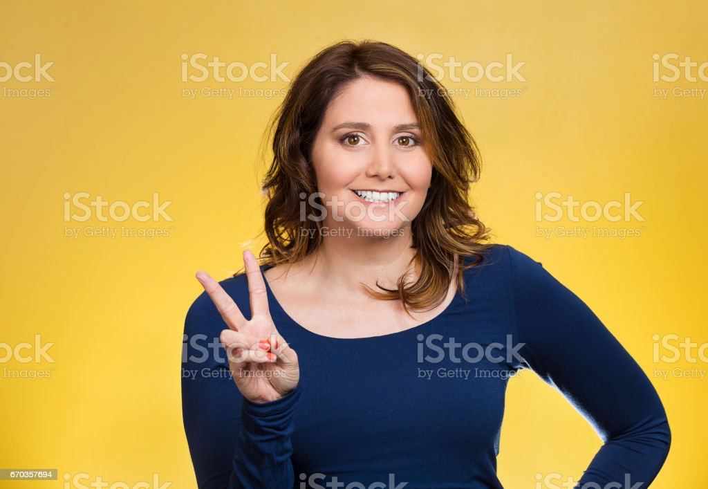 young, middle aged smiling woman, giving peace, victory, two sign, with hands stock photo