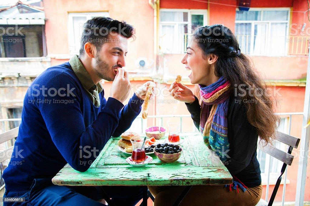 Young middle eastern couple enjoying Turkish snack on balcony stock photo