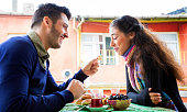 istock Young Middle Eastern couple laughing while having snack on balcony 532447827