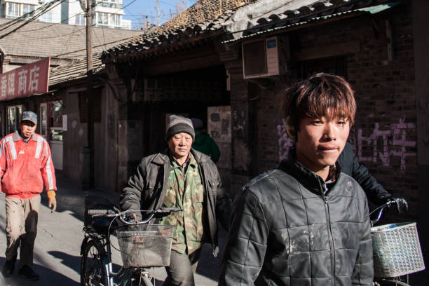 Young migrant workers walk in an Hutong alley in the cold winter in Beijing, China Beijing, China - December 26, 2013: Young migrant workers walk in an Hutong alley in the cold winter. migrant worker stock pictures, royalty-free photos & images