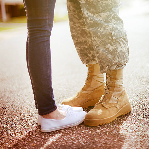 young military couple kissing each other, homecoming concept - wife stock photos and pictures
