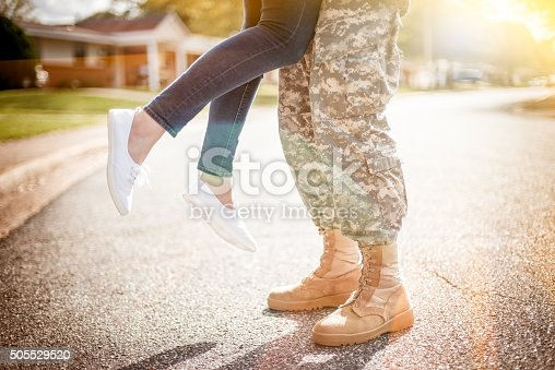 Young military couple kissing each other, homecoming concept, warm orange toning applied