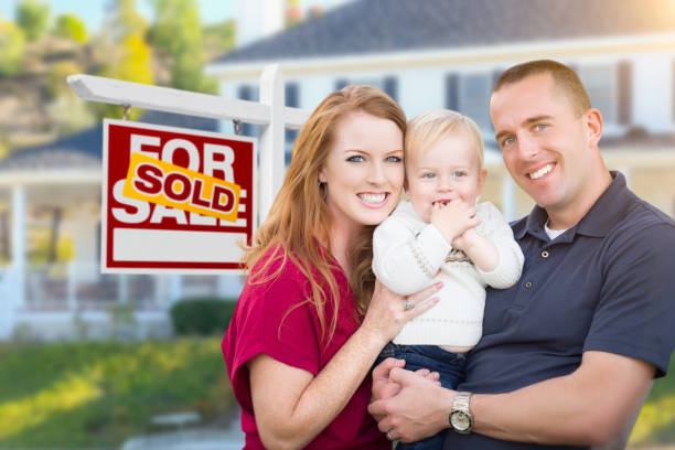 Young Military Family in Front of Sold Sign and House stock photo