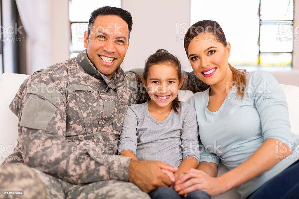 young military family sitting on sofa at home stock photo