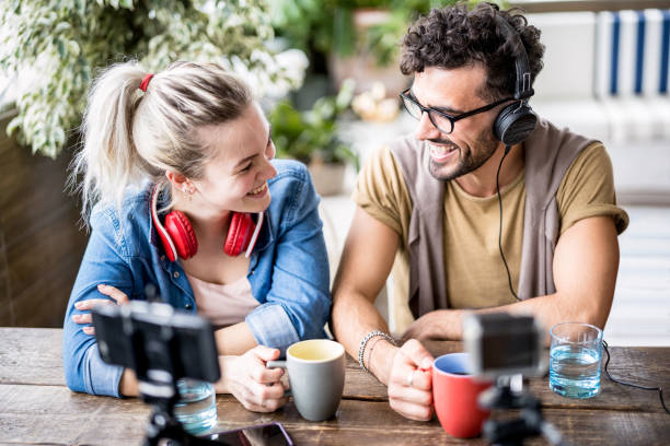 Young millenial couple sharing creative content online on webcam - Digital marketing concept with next generation influencer having fun on radio video stream - Vlogging time at startup coworking space stock photo