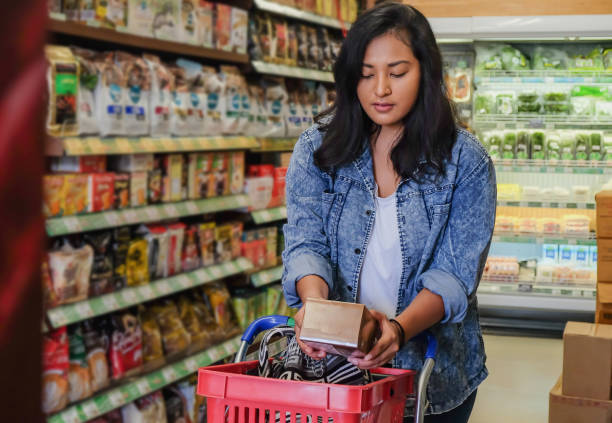 trẻ hàng thiên niên kỷ đọc nhãn thực phẩm tại siêu thị - certain food hình ảnh sẵn có, bức ảnh & hình ảnh trả phí bản quyền một lần
