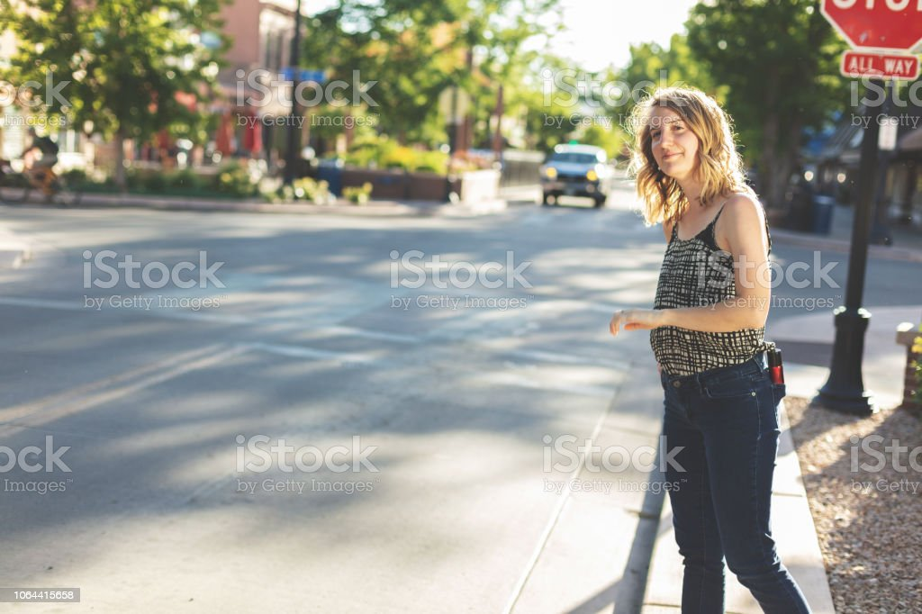 Young Millennial Age Female Crossing Urban City Street stock photo