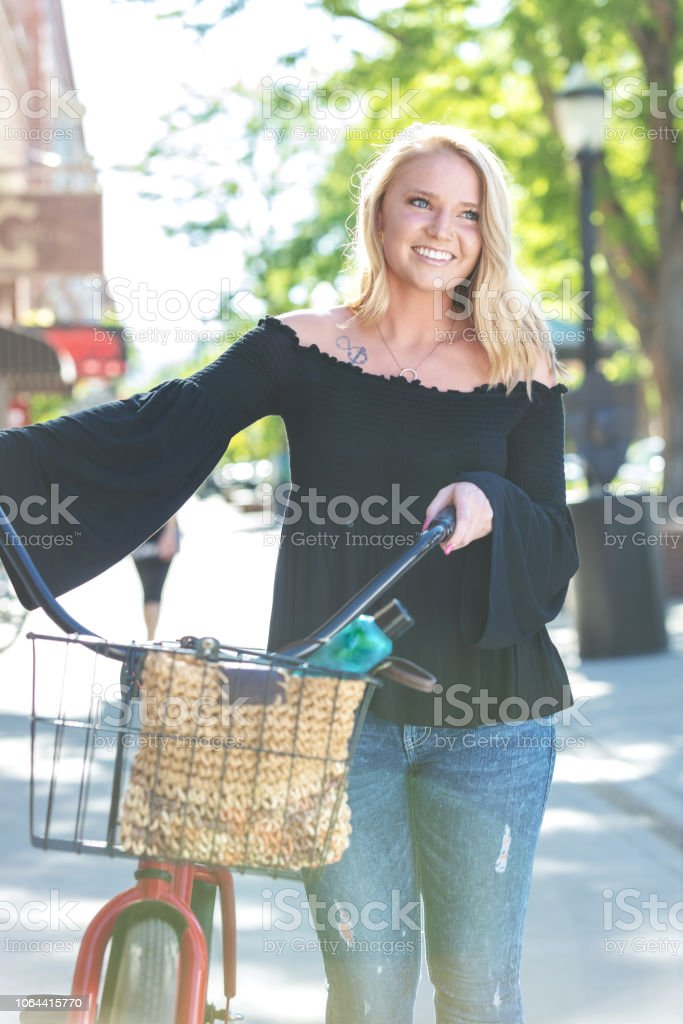 Young Millennial Age Female On Urban City Street Walking with Bicycle stock photo