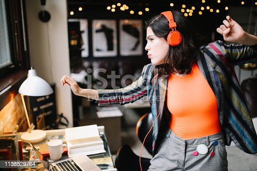 Young Latinx woman sitting at the desk in her Los Angeles apartment, receiving happy news over the social networks or just having a nice day, dancing to the music.