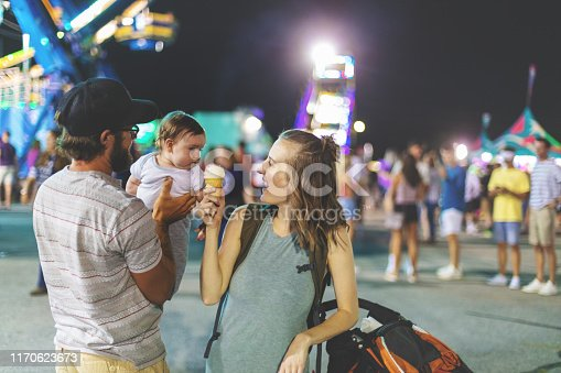 At the Empire State Fair in Springfield Missouri a Young Milennial family including father mother and baby boy enjoying their time  on a hot July summer night (Shot with Canon 5DS 50.6mp photos professionally retouched - Lightroom / Photoshop - original size 5792 x 8688 downsampled as needed for clarity and select focus used for dramatic effect)