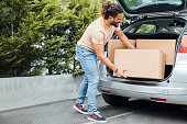 Young millennial man with long hair and a beard, putting boxes in the back of the car, moving