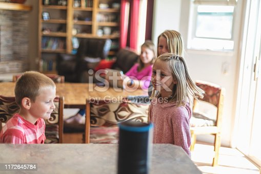 Operating a Smart Speaker with a Millennial Young Mother and Young Family at Home Secure in Western Colorado (Shot with Canon 5DS 50.6mp photos professionally retouched - Lightroom / Photoshop - original size 5792 x 8688 downsampled as needed for clarity and select focus used for dramatic effect)