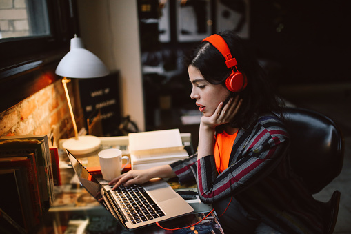 Young Latinx woman sitting at the desk in her Los Angeles apartment, working on the laptop or just having a nice day, listening to the music.