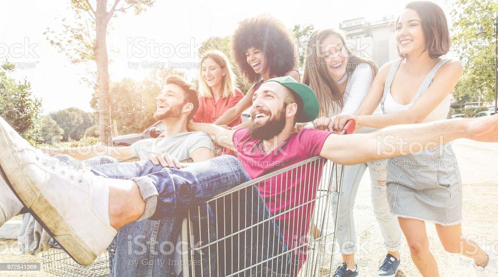 Junge Generation y Menschen Rennen mit Warenkorb - Happy verrückten Freunde Spaß mit Wagen im Parkhaus - Jugendkonzept Lifestyle und Party - konzentrieren sich auf richtige Mann Gesicht – Foto