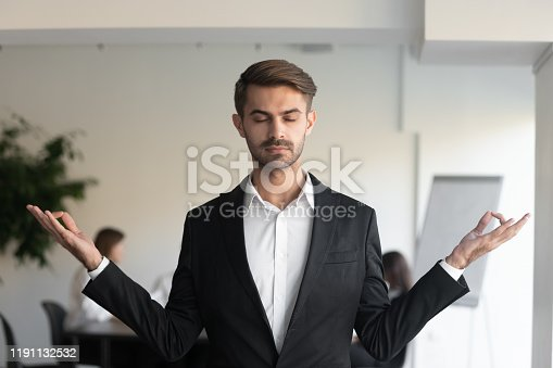 916520034istockphoto Young mindful businessman doing yoga breathing exercises. 1191132532