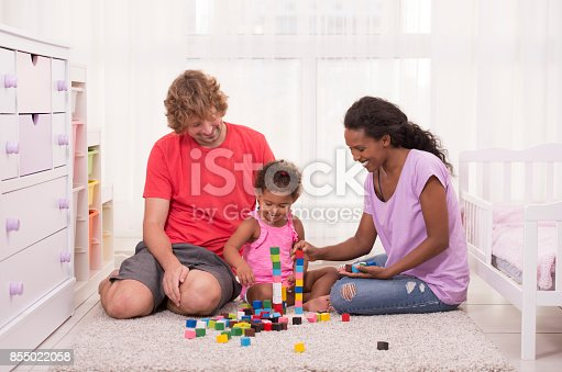 istock Young mixed family bonding playing together. 855022058