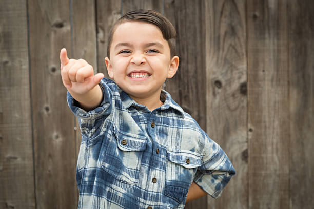 Young Mixed Race Boy Making Shaka Hand Gesture stock photo