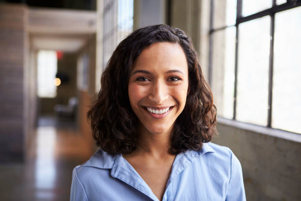young mixed race businesswoman smiling to camera - donna foto e immagini stock