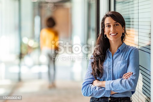 One Happy Pretty Business Woman Standing in Hall and looking at camera with smile.