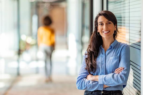 Jeune femme d'affaires mélangée de course souriant à l'appareil-photo - Photo