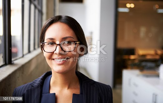 Young mixed race businesswoman wearing glasses, close up