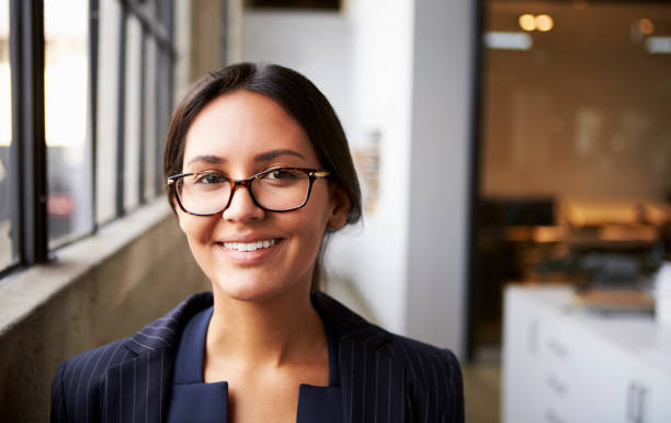 Young mixed race businesswoman wearing glasses, close up Young mixed race businesswoman wearing glasses, close up one young woman only stock pictures, royalty-free photos & images