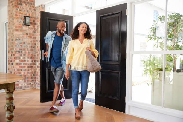 Young mixed race couple arriving at home Young mixed race couple arriving at home model home stock pictures, royalty-free photos & images