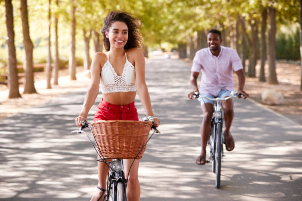 Young mixed race couple riding bicycles on a tree lined road stock photo