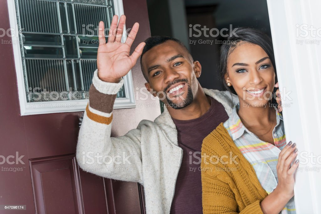 Young mixed race couple standing in front doorway waving stock photo