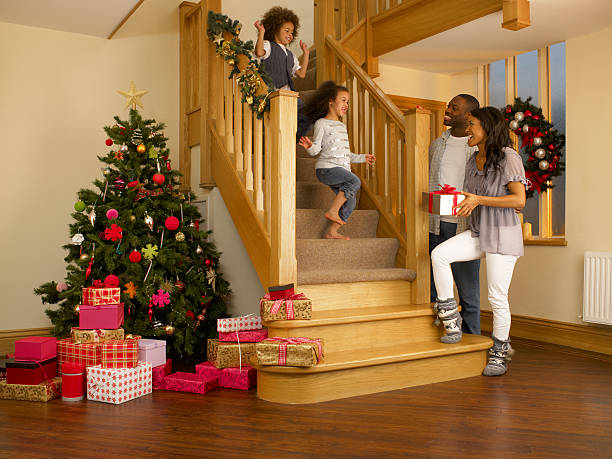 young mixed race family on christmas morning - christmas tree stockfoto's en -beelden