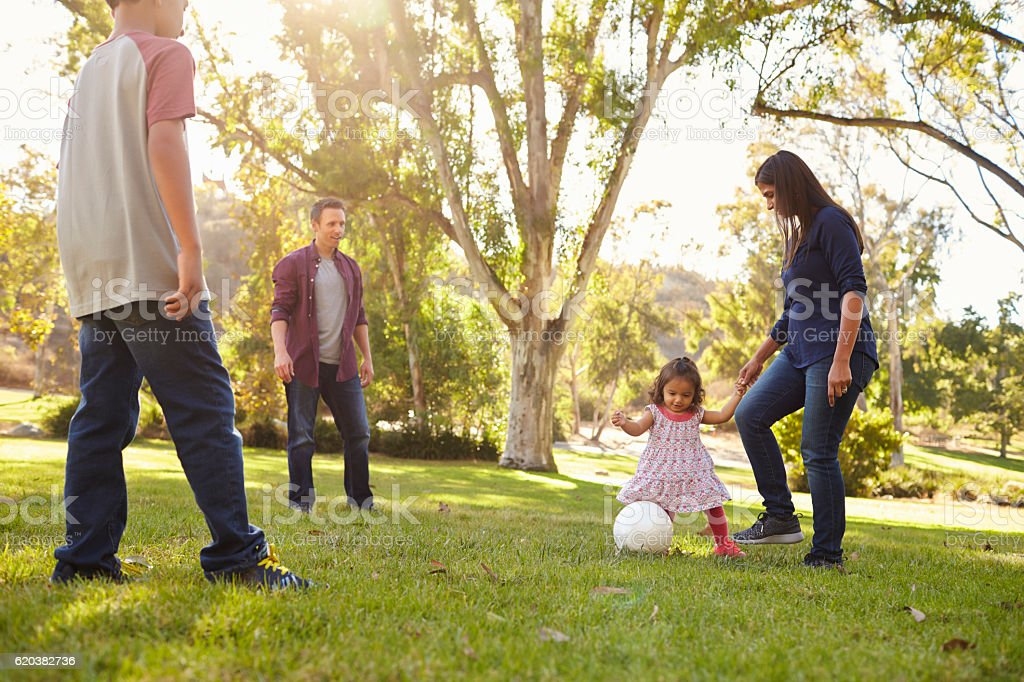 Young mixed race family playing with ball in a park - foto de stock