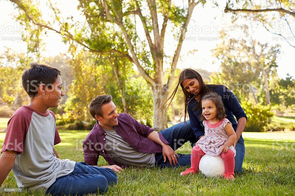 Young mixed race family relaxing with soccer ball stock photo