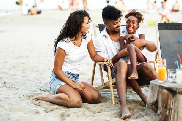 Young mixed race family sitting and relaxing at the beach on beautiful summer day. stock photo