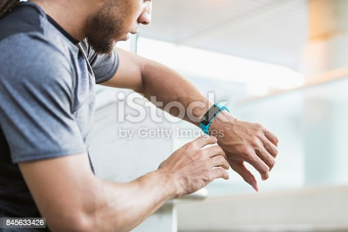 A young mixed race man, in his 20s, checking the fitness tracker on his wrist.
