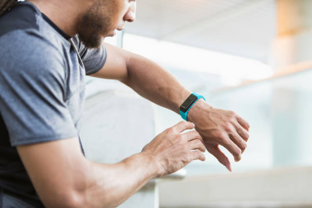 Young mixed race man checking his fitness tracker A young mixed race man, in his 20s, checking the fitness tracker on his wrist. fitness tracker stock pictures, royalty-free photos & images