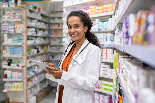Happy friendly multiethnic pharmacist doing inventory in a provided and modern pharmacy while looking at camera. Portrait of smiling young doctor woman working in drugstore with digital tablet. African smiling druggist working at hospital pharmacy.