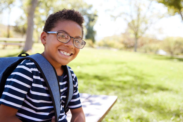 Young mixed race schoolboy in glasses smiling to camera Young mixed race schoolboy in glasses smiling to camera 12 13 years stock pictures, royalty-free photos & images