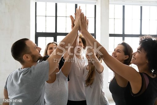 Head shot excited young mixed race sporty people joining hands in air, giving high five to each other, celebrating team success or self supporting before intensive workout in modern sport club.