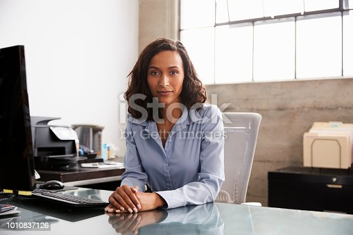 Young mixed race woman at office desk looking to camera