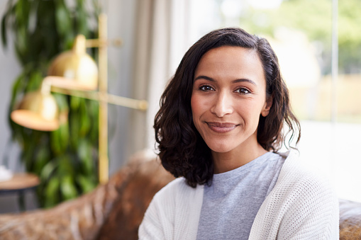 Young mixed race woman in coffee shop looking to camera