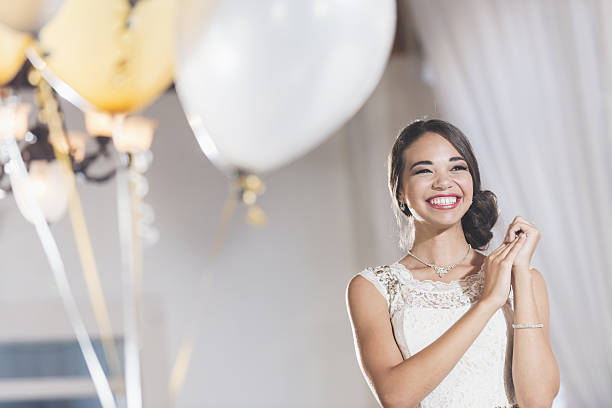 young mixed race woman in white dress at party - prom stock photos and pictures