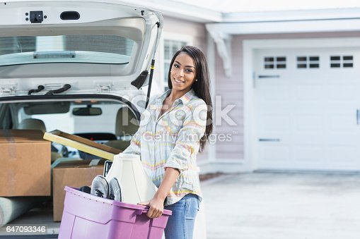 istock Young mixed race woman moving house 647093346