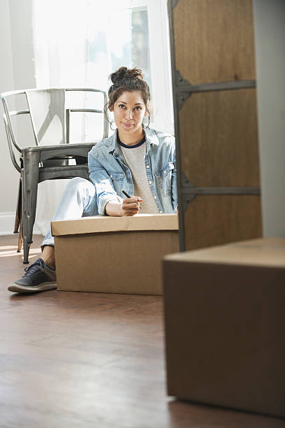 young mixed race woman moving, writing checklist - umzug checkliste stock-fotos und bilder