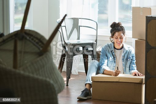 istock Young mixed race woman moving, writing checklist 638835014