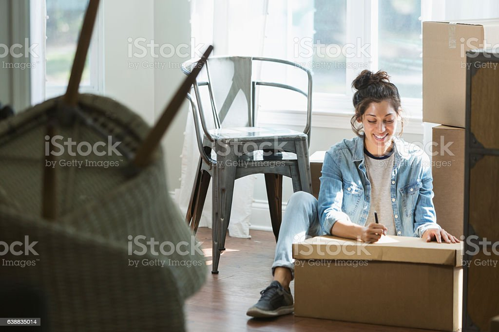 Young mixed race woman moving, writing checklist stock photo